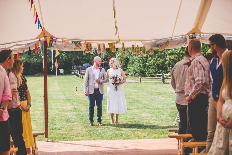 Marquee wedding with bright bunting decoration and bride wearing midi pleated wedding skirt