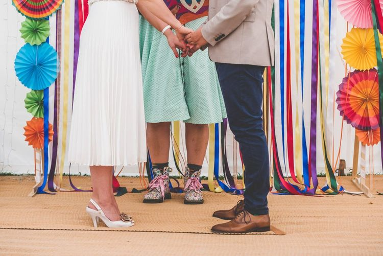 Marquee wedding with bright ribbon and paper fan decorations with midi pleated wedding skirt
