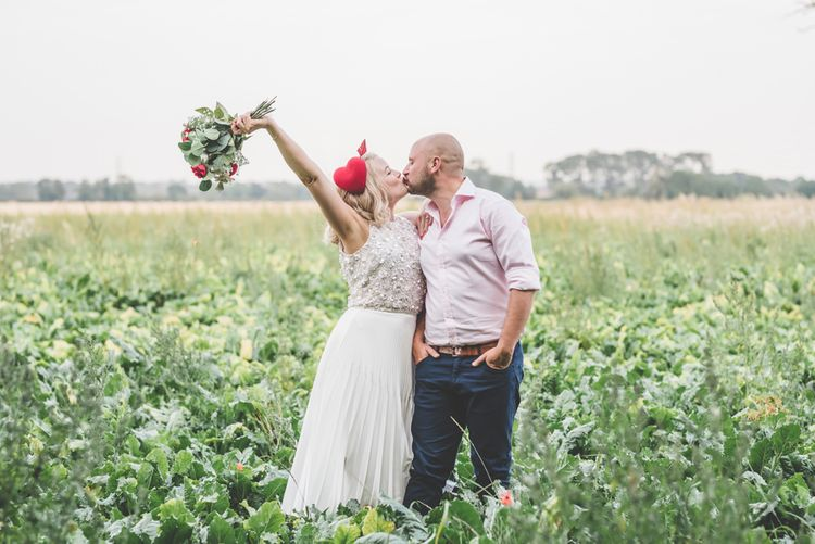 Bride and groom tie the knot with midi wedding skirt and bright heart hair decoration