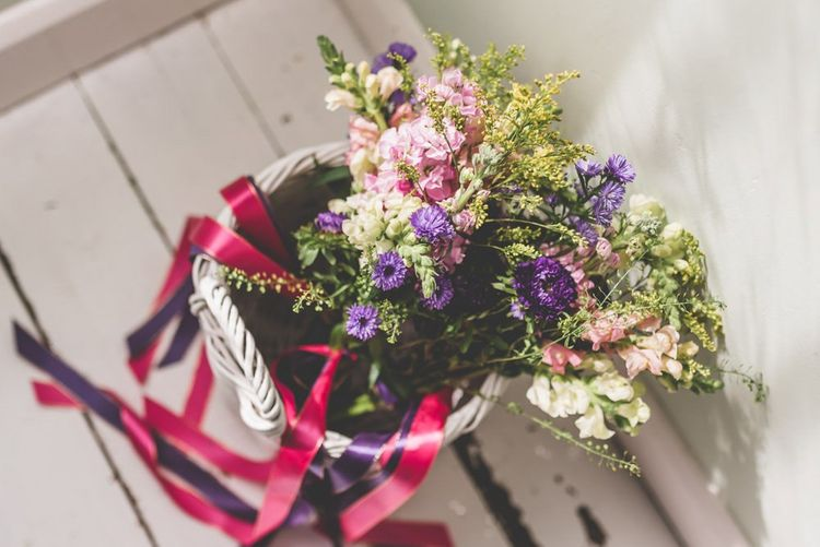 Pink and purple bridesmaid bouquets with matching ribbon decoration for fun fete themed celebration