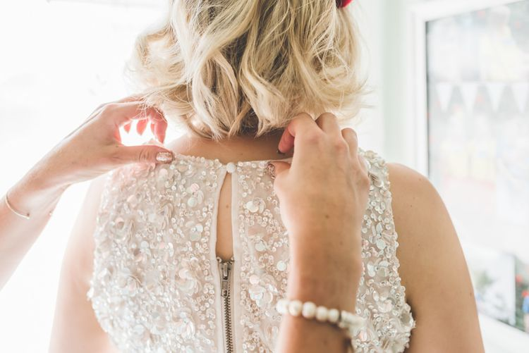 Back of brides two piece gown with pleated midi wedding skirt and embellished top