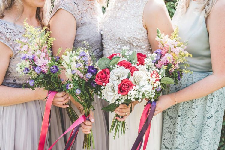 Floral bouquets with pink and purple ribbon detailing for village fete themed marquee celebration