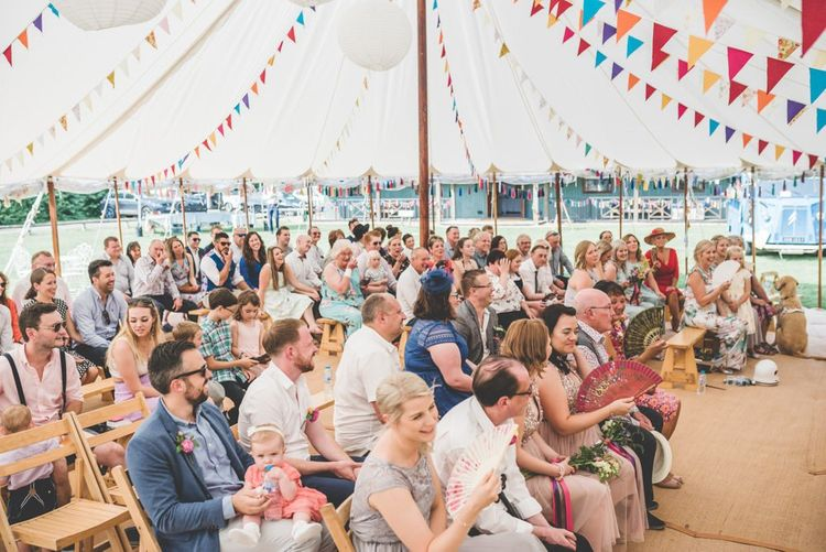 Village fete themed marquee ceremony with bright homemade bunting and paper lantern decoration