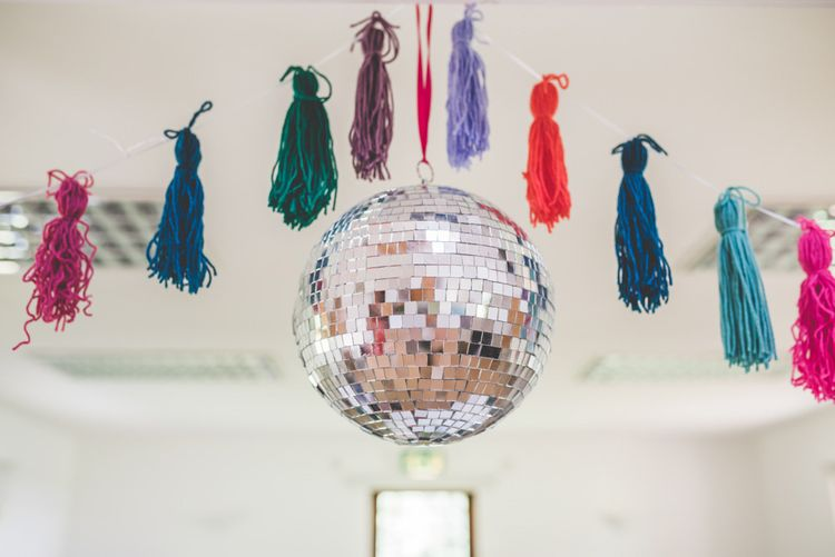Homemade colourful tassels with glitter ball decorations at fun wedding reception