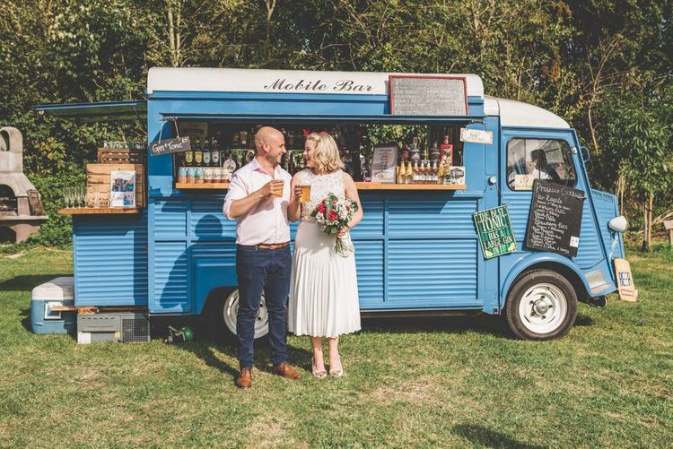 Bride wearing midi wedding skirt and groom enjoying the drinks truck at fun outdoor reception