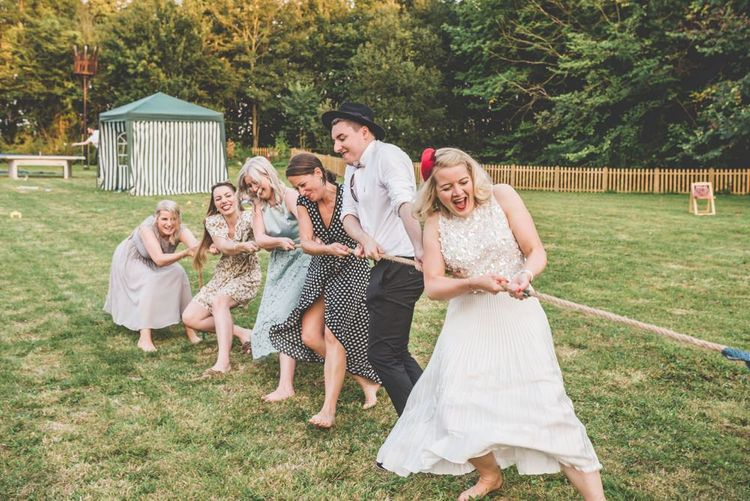 Tug of war wedding games with midi wedding skirt at this village fete themed celebration
