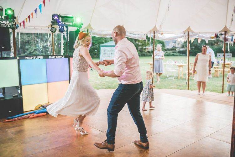 Bride and grooms first dance wearing midi wearing skirt with bight and colourful decor