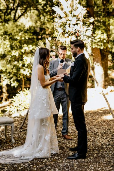 Bride in Tiered Lace Emma Beaumont Wedding Dress and Groom in Givenchy Tuxedo Exchanging Vows