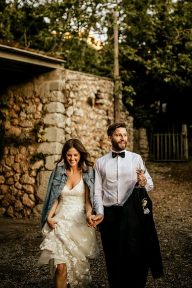 Bride in Emma Beaumont Wedding Dress and Denim Jacket and Groom in Givenchy Tuxedo Holding Hands