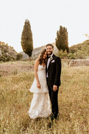 Bride in Tiered Lace Emma Beaumont Wedding Dress and Groom in Givenchy Tuxedo Embracing