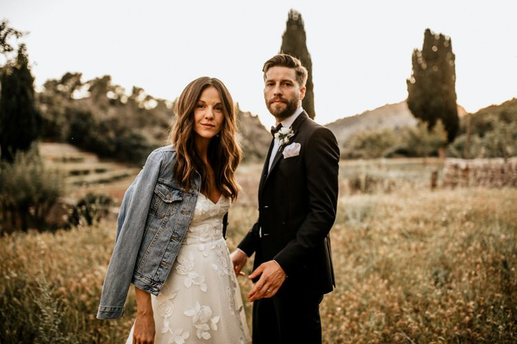 Bride in Tiered Lace Emma Beaumont Wedding Dress and Blue Denim Jacket and Groom in Givenchy Tuxedo