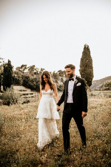 Bride in Tiered Lace Emma Beaumont Wedding Dress and Groom in Givenchy Tuxedo Holding Hands