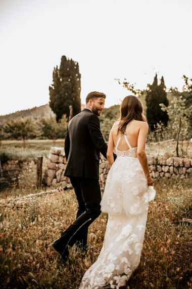 Bride in Tiered Lace Emma Beaumont Wedding Dress and Groom in Givenchy Tuxedo Walking Through Fields