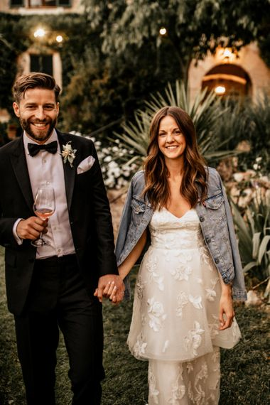 Bride in Tiered Lace Emma Beaumont Wedding Dress and Denim Jacket and Groom in Givenchy Tuxedo Laughing Whilst Holding Hands