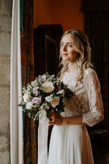 Bride in Lace Top Holding in a Cream and Purple Bouquet
