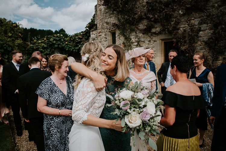 Wedding Guest in Forest Green Dress Hugging the Bride
