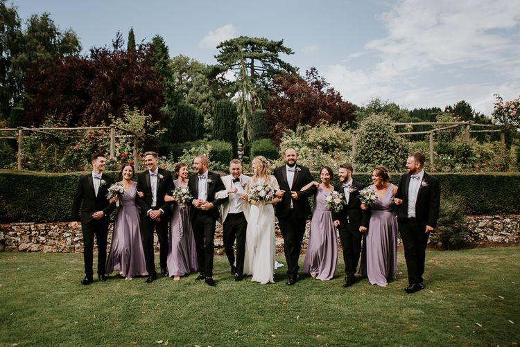 Sophisticated Wedding Party in Black Tuxedos and Purple Bridesmaid Dresses
