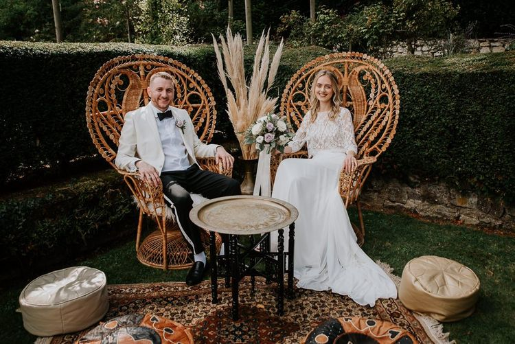 Bride and Groom Sitting in Chill Out Area with Peacock Chairs, Moroccan Rugs and Poufs