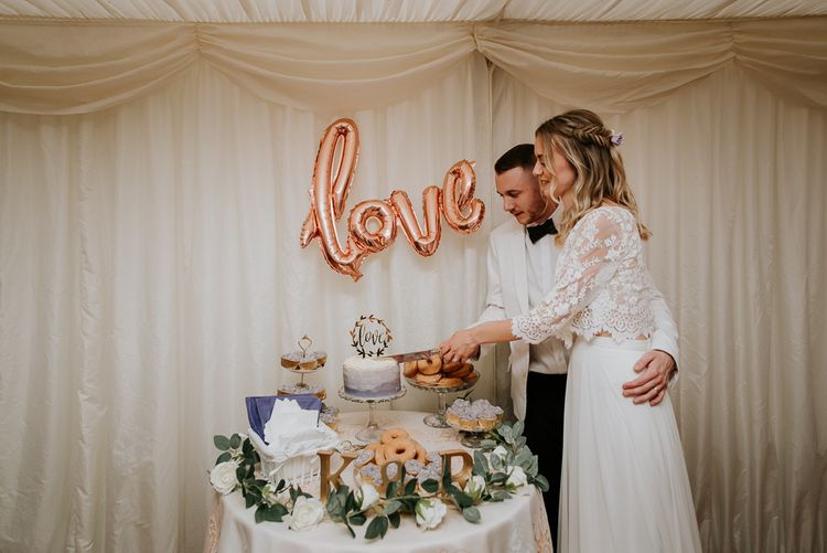 Bride and Groom Cutting the Wedding Cake with Gold Foil Love Balloon as Cake Table Backdrop