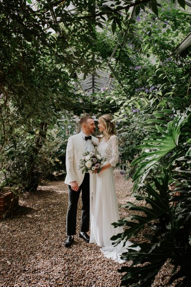 Bride in Wendy Makin Bridal Separates and Groom in White Dinner Jacket Embracing Under  Some Greenery