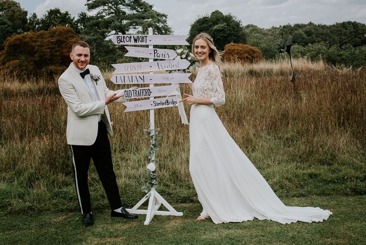 Bride in Wendy Makin Bridal Separates and Groom in White Dinner Jacket Standing Next to a Sign Post