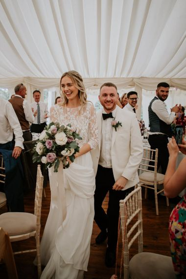 Bride in Separates and Groom in White Dinner Jacket Entering the Marquee Wedding Reception