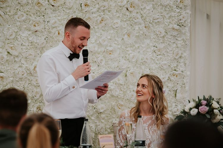 Groom in Bow Tie Giving His Wedding Speech in Front of a White Flower Backdrop