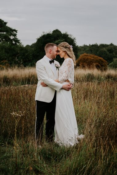Bride in Lace Top and Plain Skirt by Wendy Makin  with Groom in White Dinner Jacket and Bow Tie Embracing in a Field