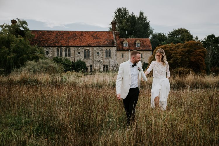 Bride in Lace Top and Plain Skirt by Wendy Makin with Groom in White Dinner Jacket and Bow Tie  Hand in Hand  in a Field