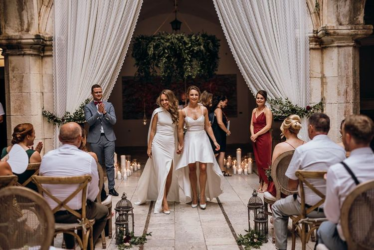 Bride in high low wedding dress walks down the aisle with her new wife