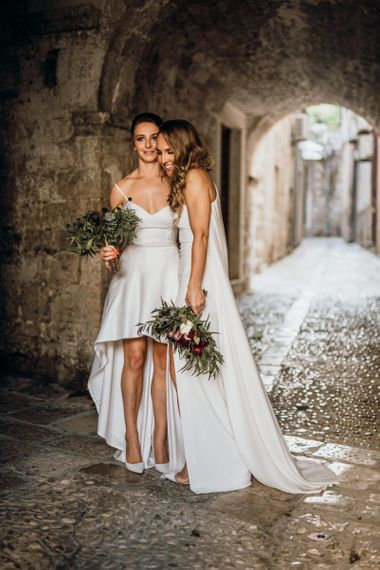 Brides in bespoke dressed with high low wedding dress and bridal cape