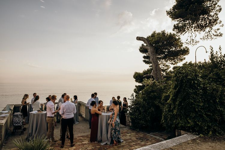 Guests enjoy drinks at destination wedding with sea views