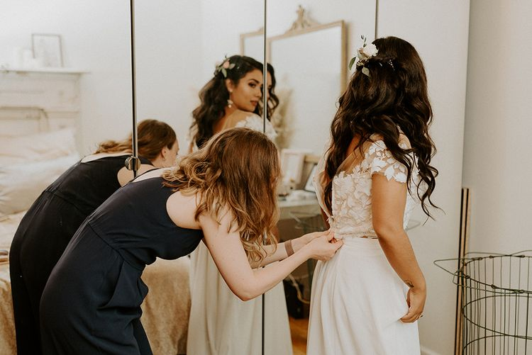 Bride putting on lace top bridal separates with flower hair decoration