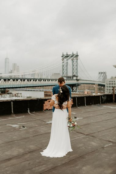 Bride and Groom embrace for first look moment on rooftop building with Manhattan skyline