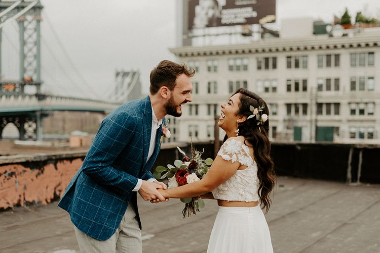 Bride and Groom first look moment on rooftop building with Manhattan skyline and king protea bouquet