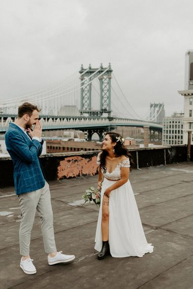 Bride and Groom first look moment on rooftop building with Manhattan skyline  and bridal boots