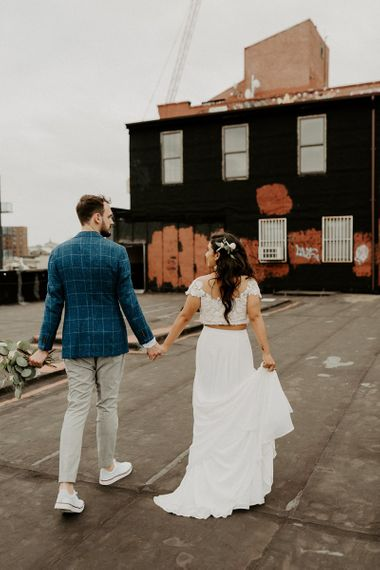 Bride and Groom first look moment on rooftop building with Manhattan skyline and back of bridal separates