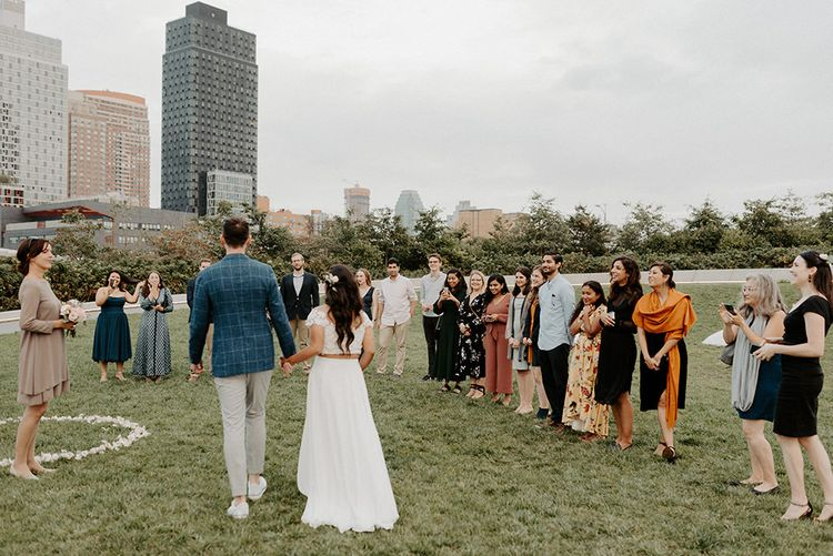 Bride and groom arriving at small ceremony with a semi circle of closes friends and family and NYC skyline backdrop