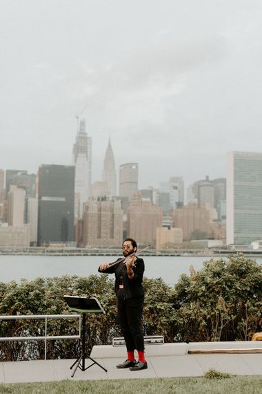Violinist at Brooklyn elopement with NYC skyline backdrop