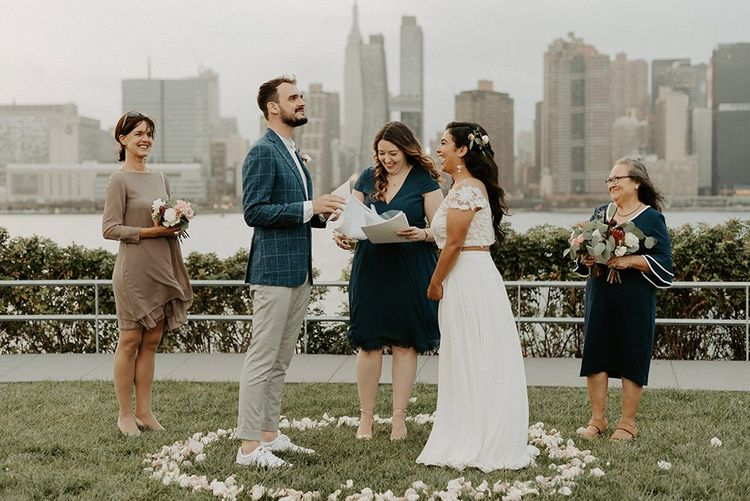 Bride and groom tie the knot at a park overlooking the East River and the NYC skyline  with groom in trainers