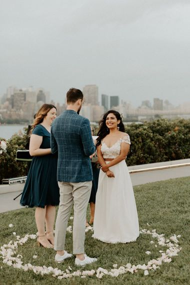 Bride and groom tie the knot at a park overlooking the East River and the NYC skyline with Groom in blazer