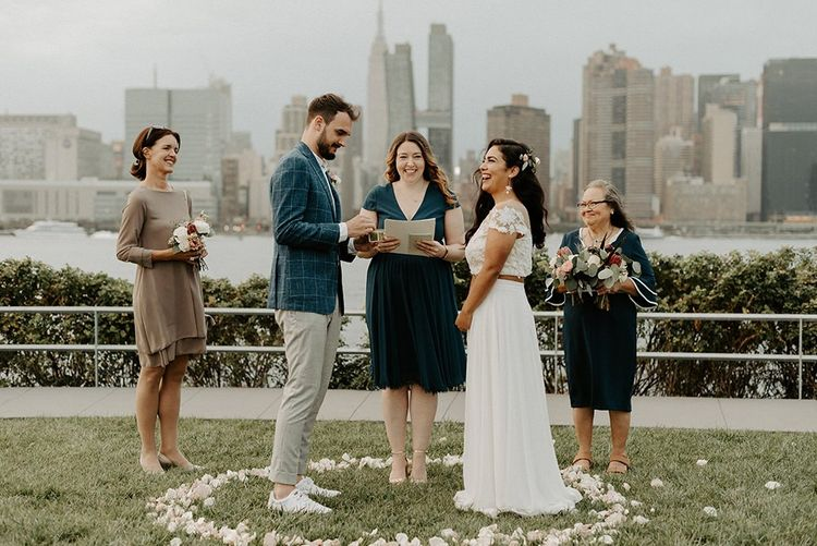 Bride and groom tie the knot at a park overlooking the East River and the NYC skyline with bridal separates