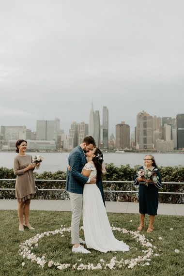 Bride and grooms first kiss at a park overlooking the East River and the NYC skyline