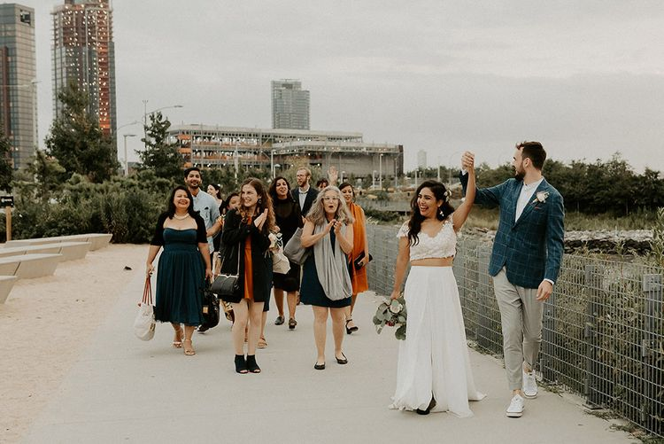 Bride and groom celebrate with their guests for Brooklyn elopement with NYC skyline backdrop
