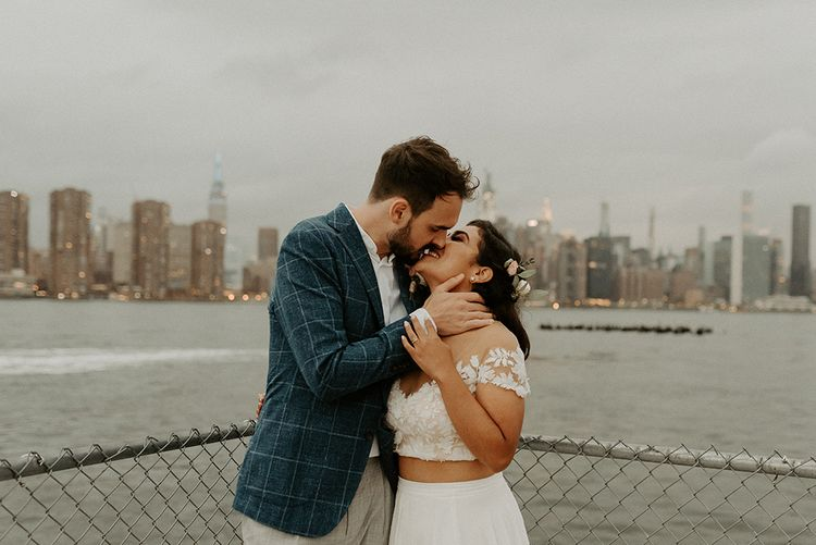 Bride and groom embrace with the NYC skyline backdrop