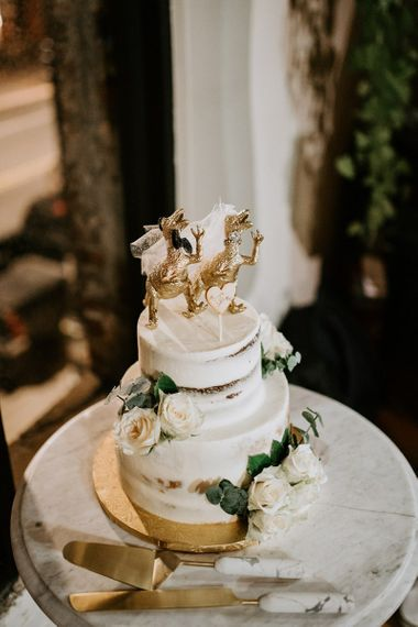 Semi naked wedding cake with dinosaur cake topper