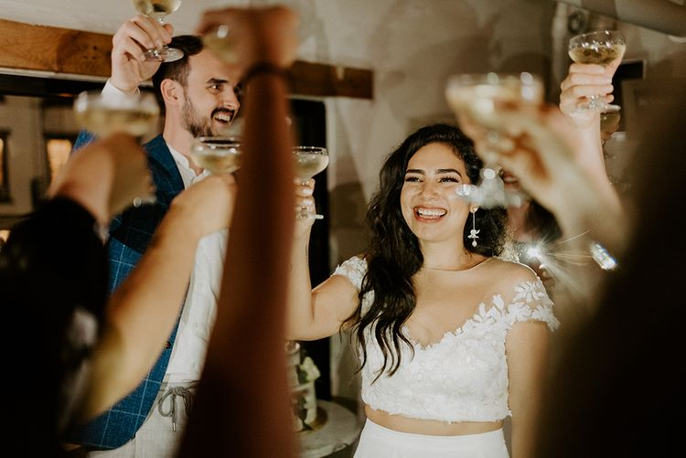 Bride and groom raise a glass with their closest friends and family
