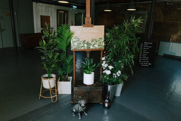 Wedding welcome sign surrounded by foliage and customised neon sign