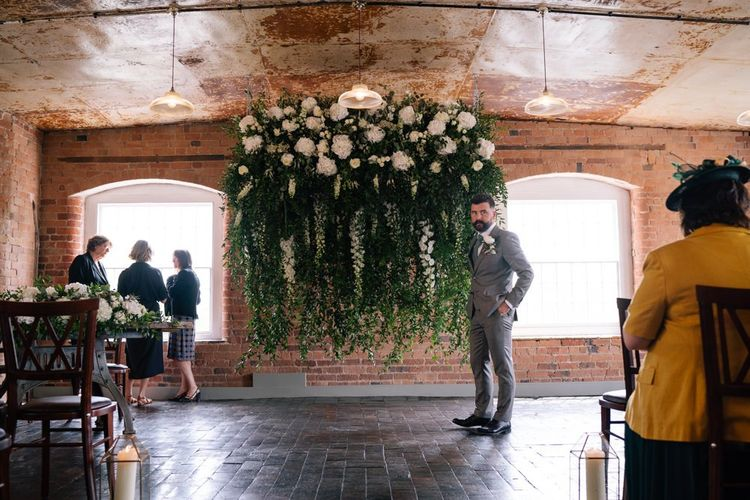 Groom waits in front of white flower installation