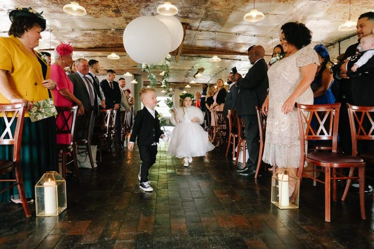 flower girl and page boy walk down the aisle with wedding balloons